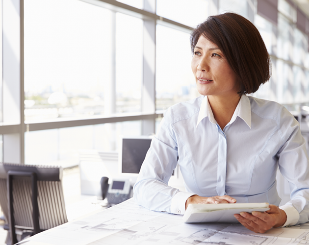 Middle-aged woman at desk with paperwork.