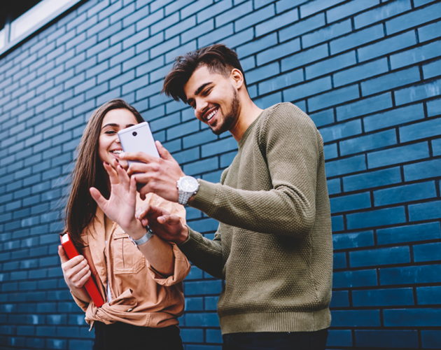 Male and female college students laughing and looking at smartphone.