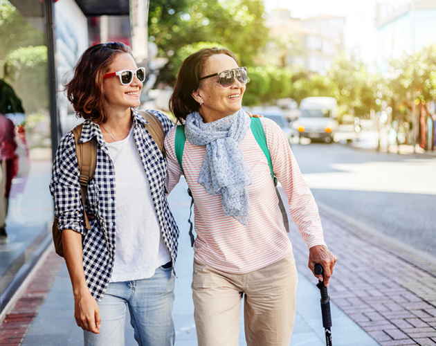 Adult woman walking down city street with her elderly mother.