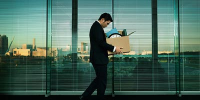 Asian worker leaving office with box after layoff and worrying about whether his credit insurance will cover his needs