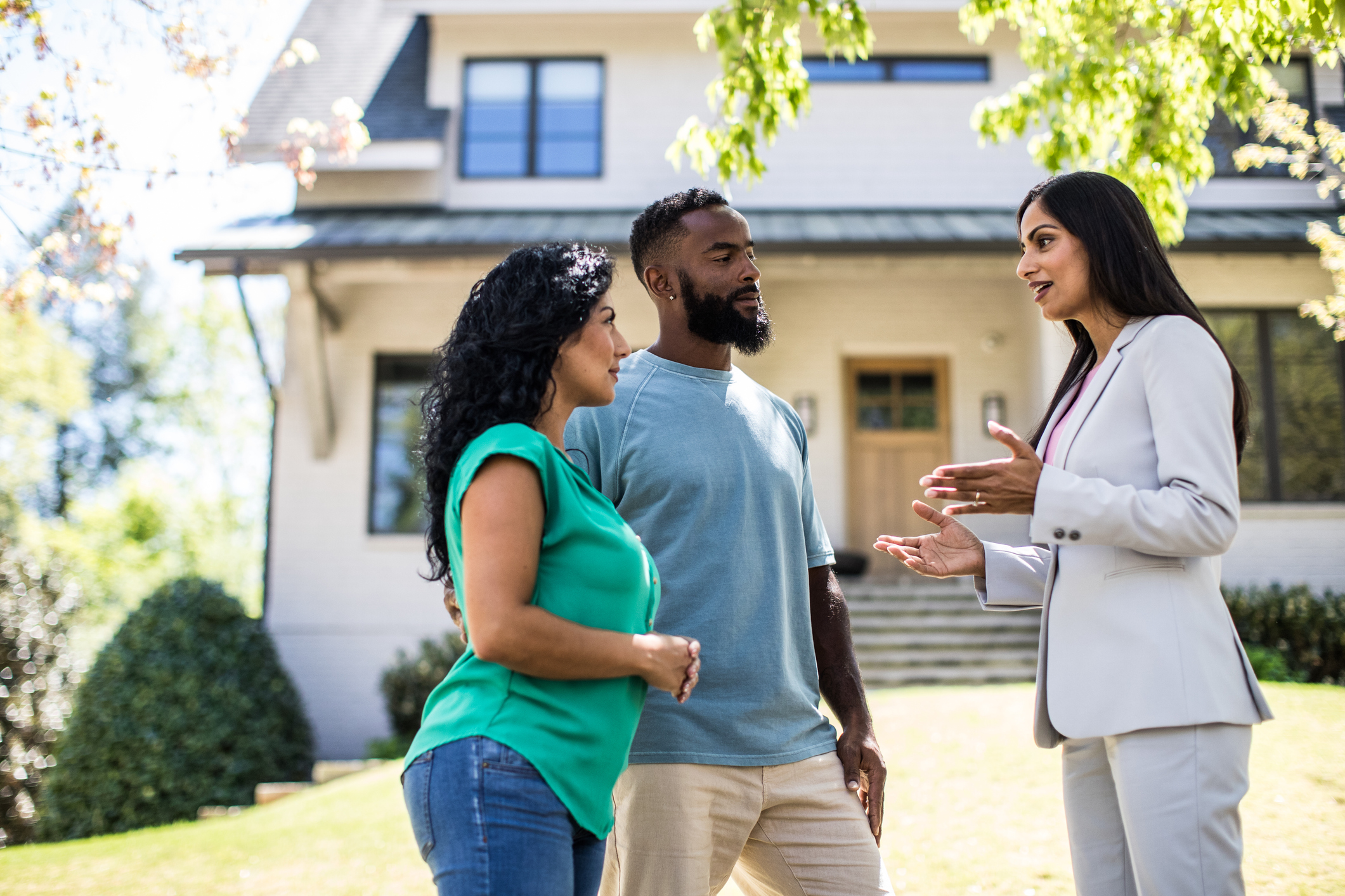 A couple discussing a real estate property with an agent prior to purchasing the property.