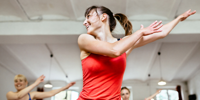 Young woman in a red tank top exercising in an aerobics class.