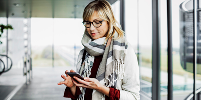 College-age student in a scarf and glasses, slightly smiling and looking at her phone.