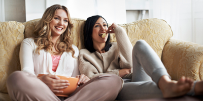Two college-age girls sitting on a couch, enjoying potato chips and a movie.