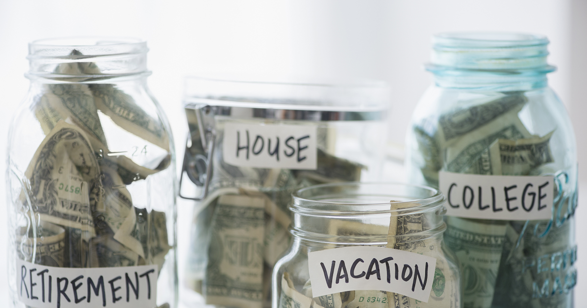 Dollar bills in glass jars labeled retirement, house, vacation and college.