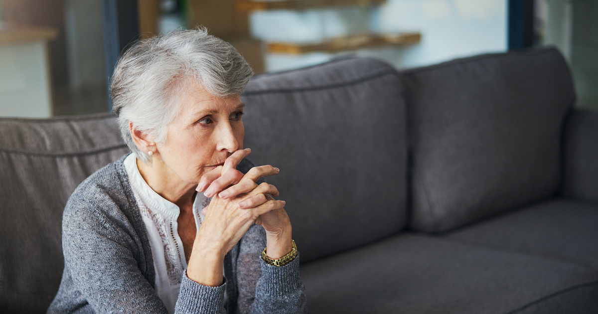 Worried senior woman sitting on couch.