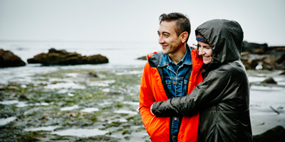 Couple walking in raincoats, arm in arm, along a rocky beach.
