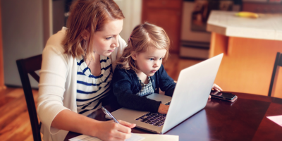 Mother sitting with her young child on her lap as they budget on the laptop.
