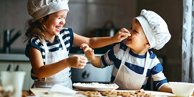 A sister and her brother cooking in the kitchen, making a mess and laughing.