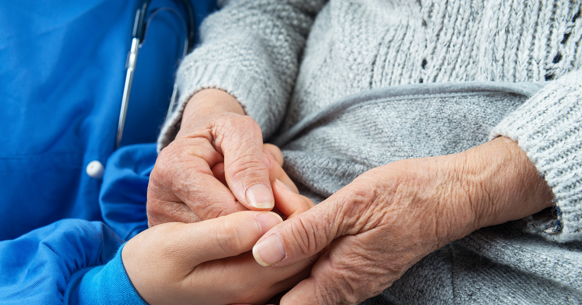 Close up of a hospice worker holding an elderly patient's hands.