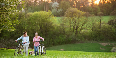A man and woman walk their bikes through a meadow while walking their dog