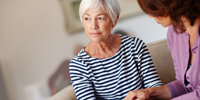 Older woman with a serious expression sitting on couch with a middle-aged woman and gazing into the distance.