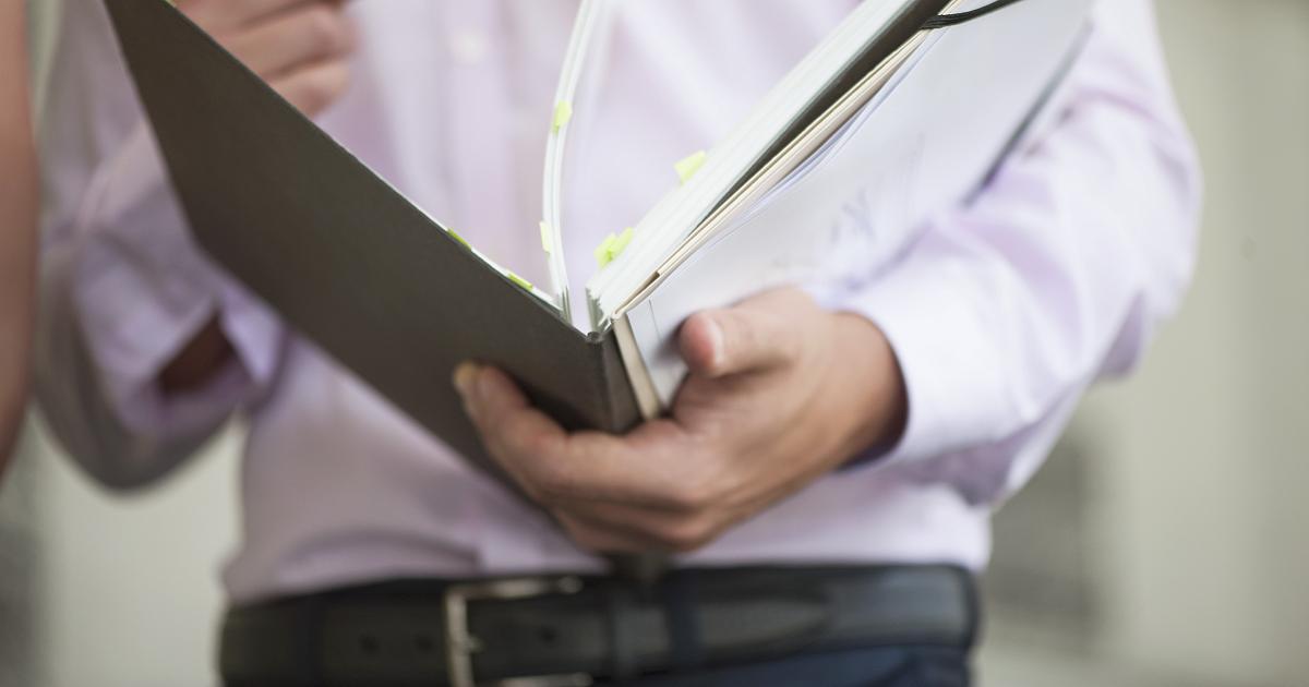 Man flipping through binder of paperwork.