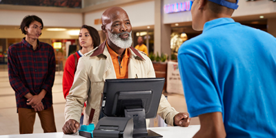 Older African-American man making purchase at kiosk in the mall.