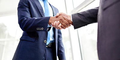 Two men shaking hands to indicate developing a financial plan