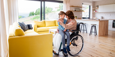 Woman in wheelchair with a young girl on her lap in an open and sunny living space.