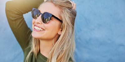 Pretty young woman with sunglasses on, smiling and looking up into the sky.
