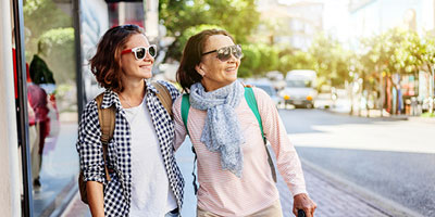 Grandmother and college-age granddaughter walking down city street wearing sunglasses and backpacks