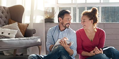 A young couple sits on the floor, smiling and looking at a notebook and iPad, as if creating a household budget.