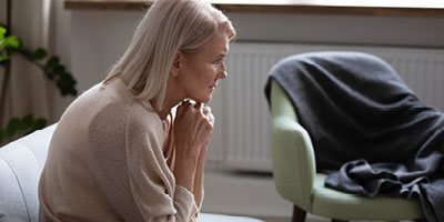 Worried woman sitting on couch thinking about how her chronic illness will affect her finances.