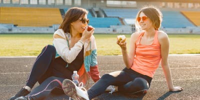 Mother and her college-aged daughter resting after a run.