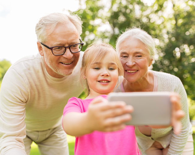 Grandparents taking a selfie with young granddaughter.