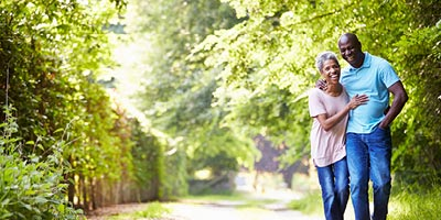 African American couple, arm in arm, walking in a park on the beautiful day.