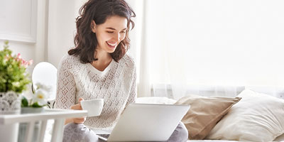 Woman drinking a cup of coffee and happily researching something on her laptop.