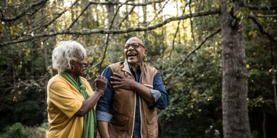 African American senior couple enjoying a walk in the woods together.