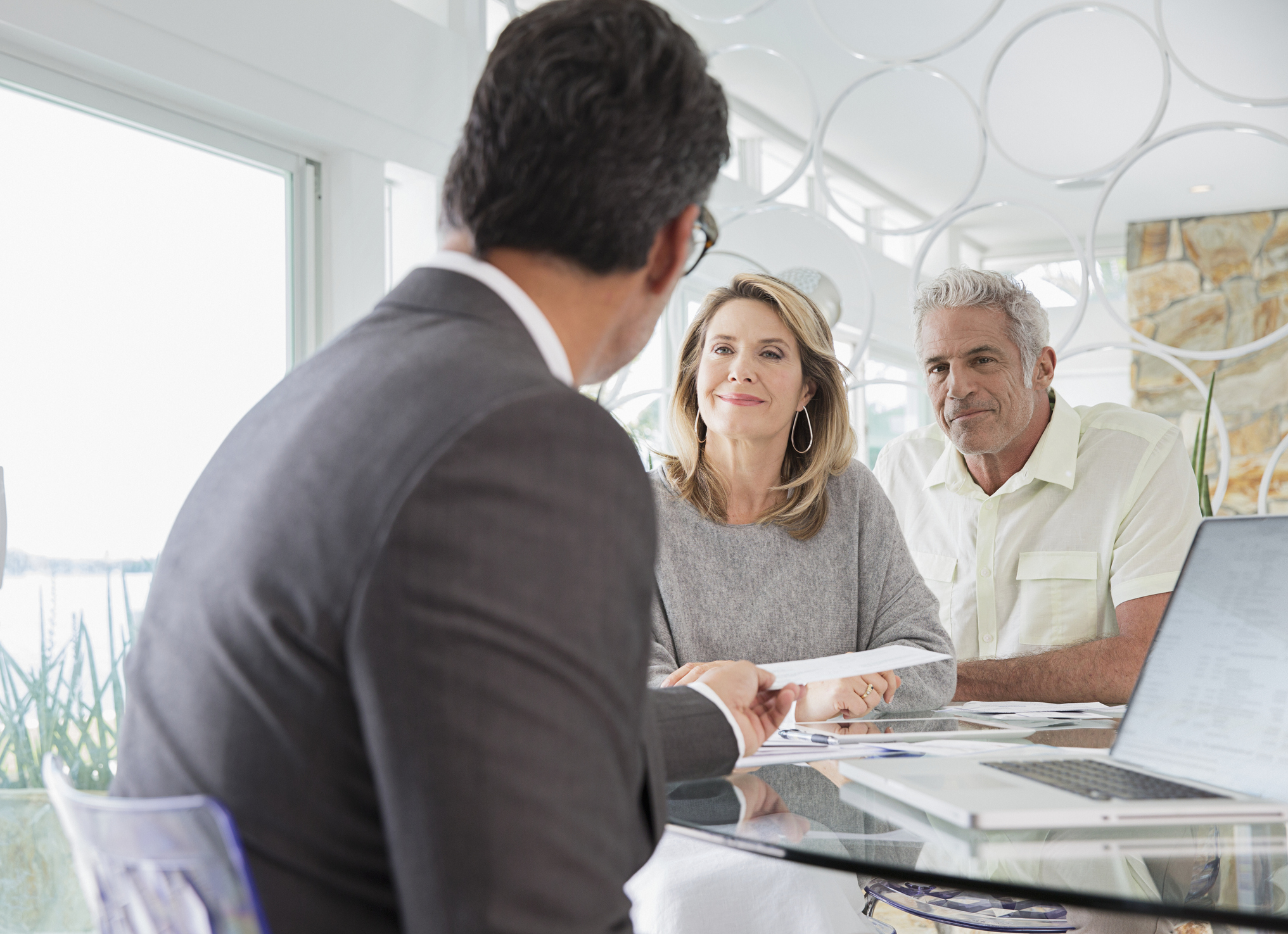 A senior couple meeting with a financial advisor, smiling as they have no regrets about retirement.