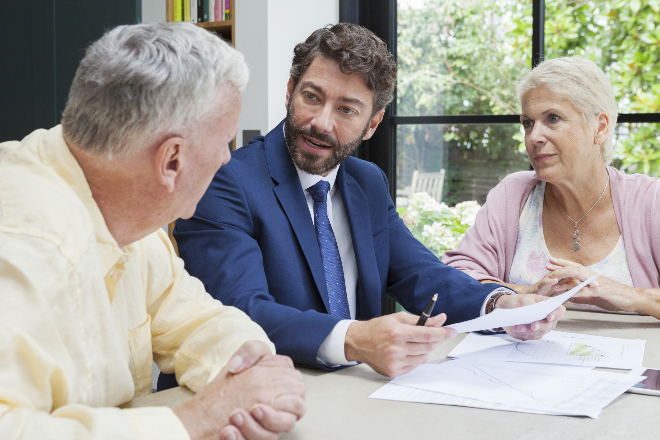 Young male financial professional sitting with a senior couple.