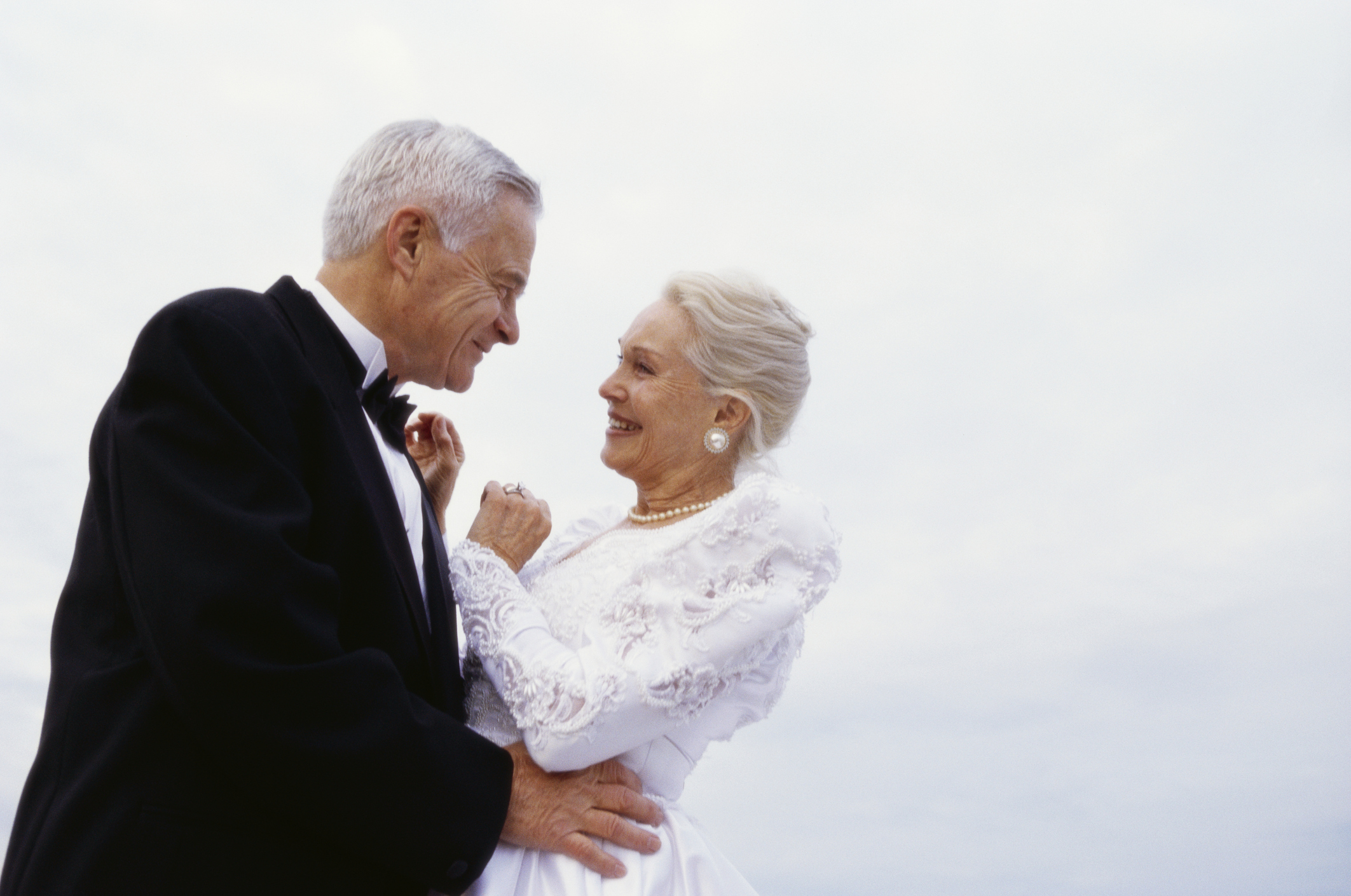 A newlywed senior couple on the beach in their wedding outfits smiling lovingly at each as they dance.