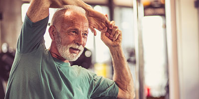 Man in his seventies stretching, as if preparing to work out.