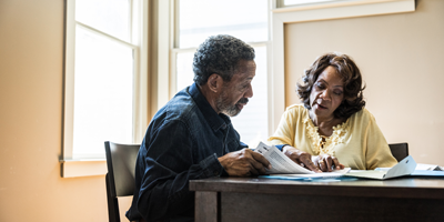A senior adult couple sitting at their kitchen table while reviewing financial paperwork.