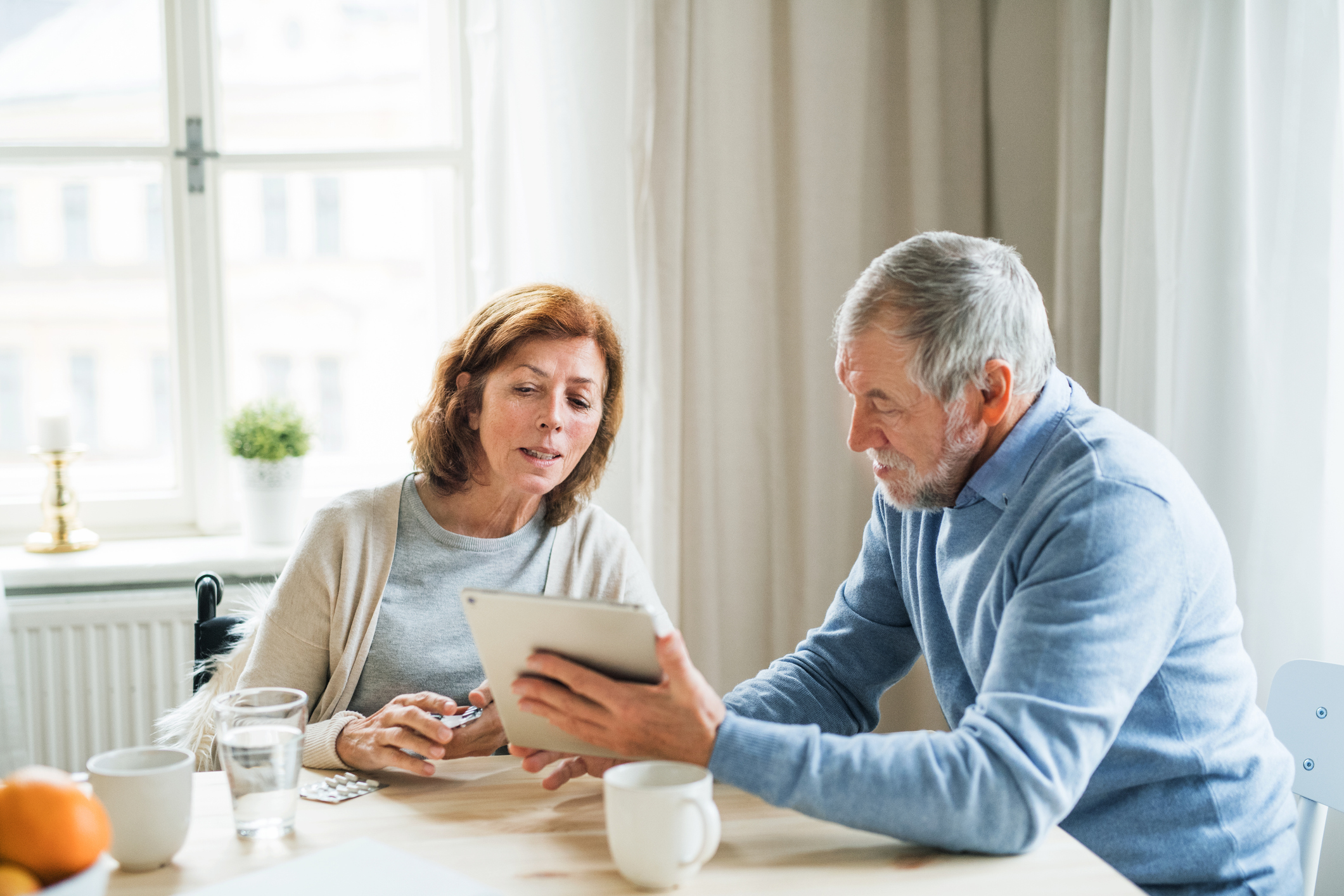 A middle-aged married couple sitting together at their kitchen table and discussing their retirement planning checklist.