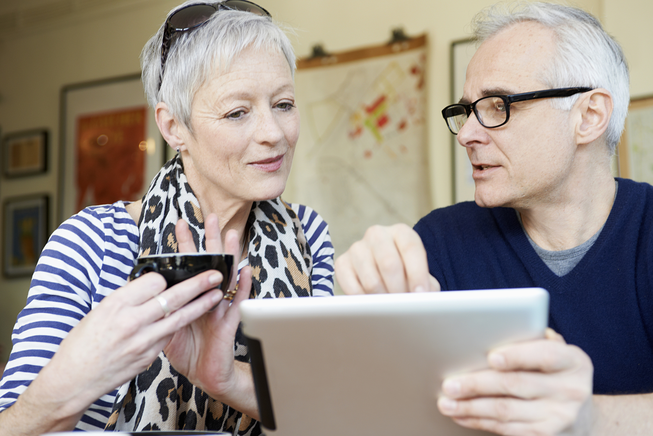 An older couple studies a tablet while searching for information.