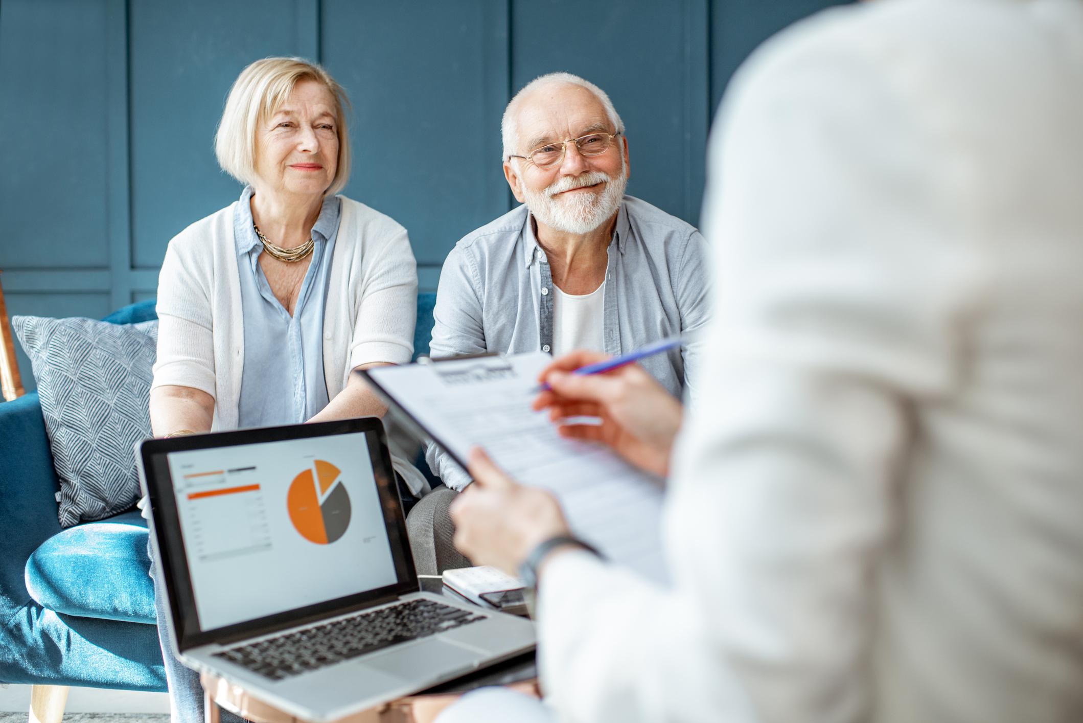 A senior couple meets with their financial advisor.