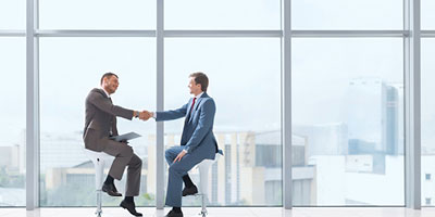 Two businessmen on tall stools, shaking hands in front of the window of an office building.