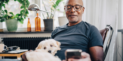 Africian-American man sitting in his home office with dog on his lap.