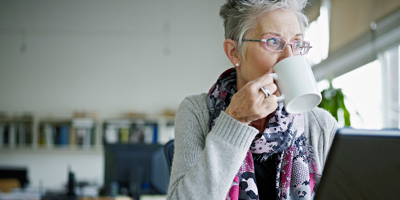 Older woman sitting at her computer and drinking coffee.
