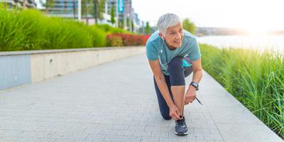 Fit older man on a jog bending down to tie shoe.