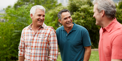 A group of middle-aged men walking on a golf course and engaged in conversation.