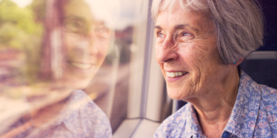 Face of an old woman looking out the window, smiling contently.