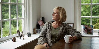 Mature woman drinking coffee and looking out the window as she thinks over her retirement plan.