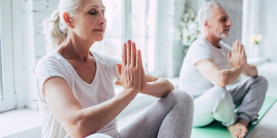 Retired woman doing yoga and resting because she has an emergency fund.