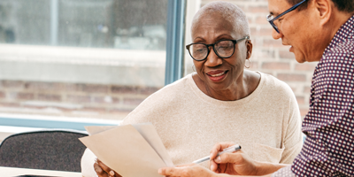 A senior adult African American woman meeting with her financial advisor to discuss immediate annuities.