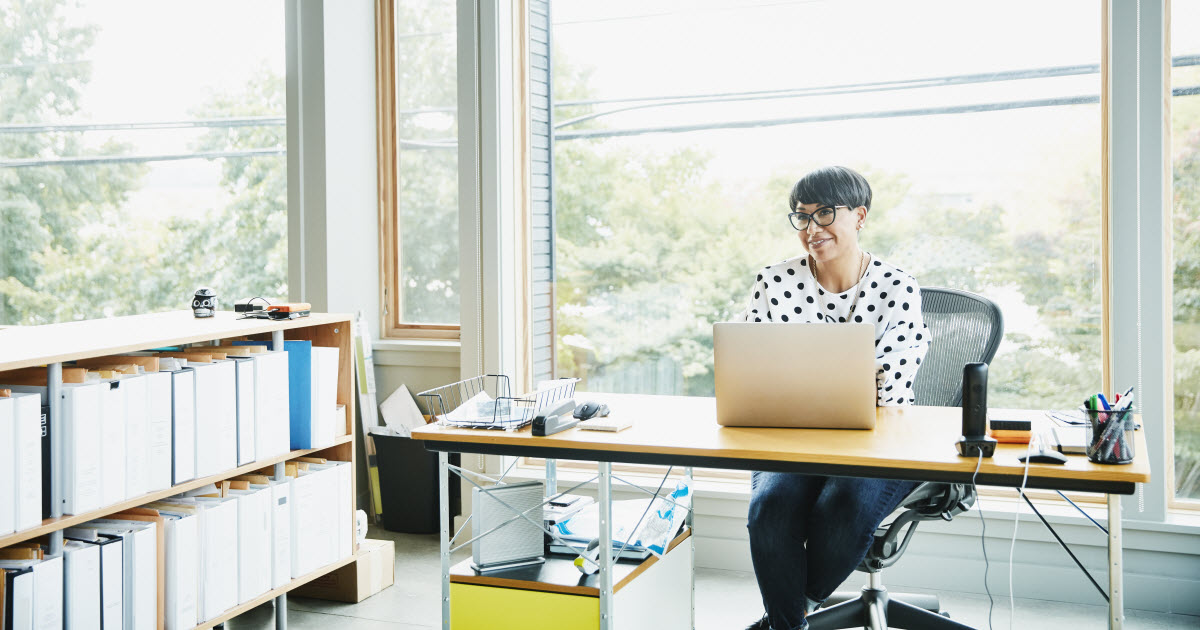 Female business owner sitting at desk in sunny office