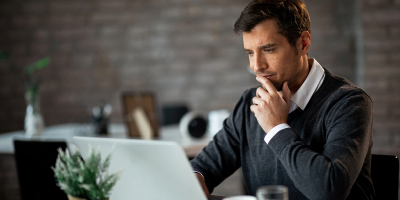 Man in a gray sweater thoughtfully looking at his laptop, as if studying information.