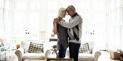 Senior couple dressed in gray, dancing and smiling in their living room.