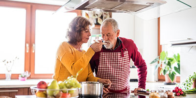 An older couple in their sixties or seventies cooking together.